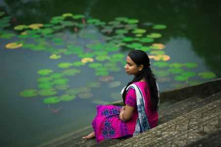 woman in pink sari dress sitting on stair beside body of water